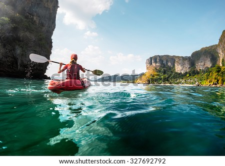Lady paddling the kayak in the calm tropical bay at sunset
