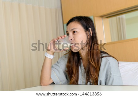 Lady patient drink a glass of milk in hospital - stock photo