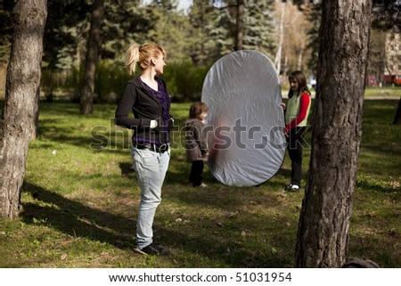 Lady posing at camera with the reflector in back - stock photo