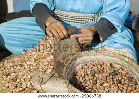 Lady racking argan nuts by hand with a stone - stock photo