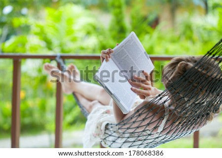 Lady reading the book in the hammock - stock photo