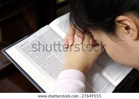 Lady resting head on bible praying