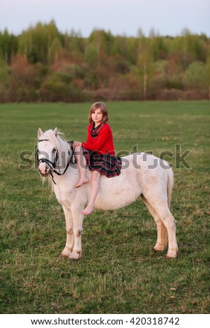 Lady riding a girl child in a dress riding a white horse Outdoors