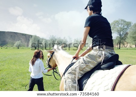 Lady riding on the horse with her trainer outdoors. Natural light and colors - stock photo
