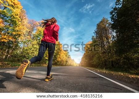 Lady running along the road in the autumn forest - stock photo