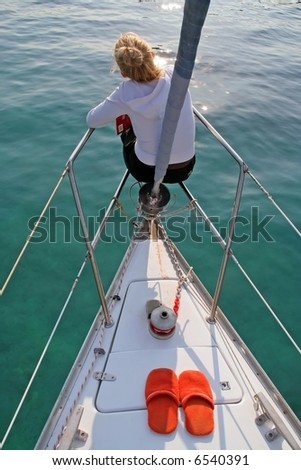 Lady sitting at the front side of yacht - stock photo