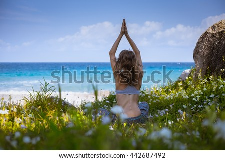 Lady sitting on the grass near ocean and doing yoga exercise