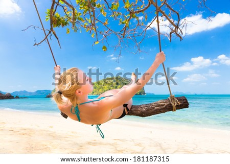 Lady swinging on the picture perfect tropical beach with the view of the island and turquoise coral reef on a sunny summer day.