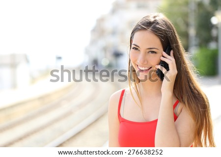 Lady talking on the mobile phone while is waiting in a train station in summer - stock photo