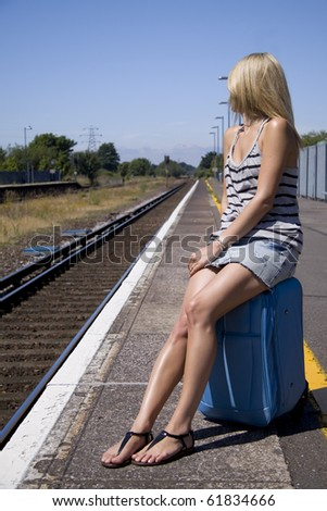 Lady waiting for train sitting on her luggage