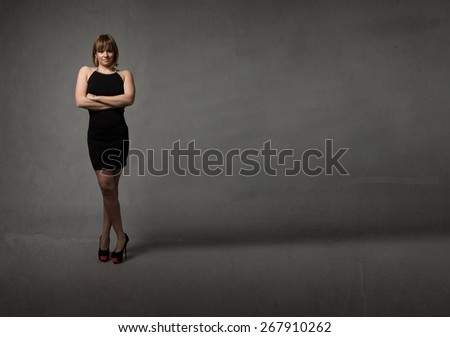 lady waiting with crossed arms, dark background - stock photo