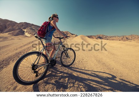 Lady with bicycle in the desert at sunny day - stock photo