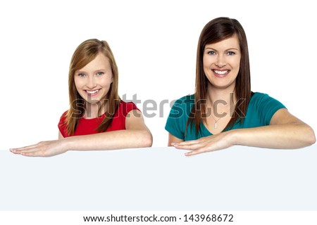 Lady with daughter posing behind blank billboard - stock photo