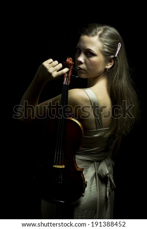 Lady with red violin in hand  in the dark