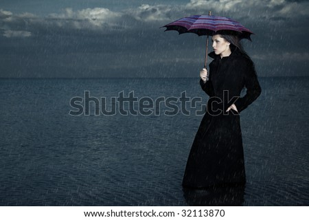 Lady with umbrella standing under the rain in the sea