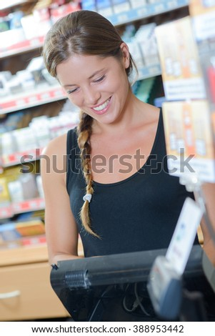 Lady working the till in a tobacconists - stock photo