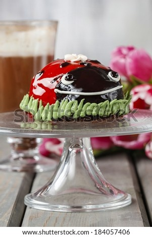 Ladybug cake and cup of hot chocolate in the background - stock photo