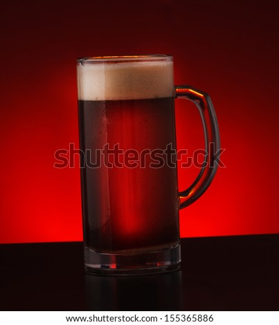 Lager draft beer isolated on dark background. Glass of beer.