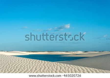 Lagoons in the desert of Lencois Maranhenses National Park, Brazil, low, flat, flooded land, overlaid with large, discrete sand dunes with blue and green lagoons