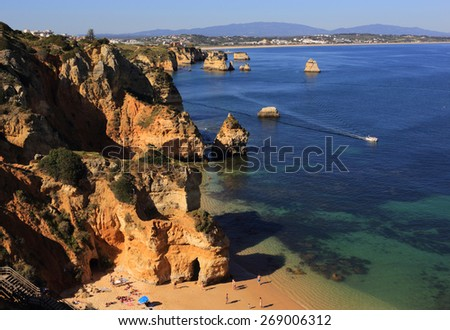 LAGOS, PORTUGAL - APRIL 01: Cliff top view of tourists sunbathing in the warm, spring sunshine on Camilo Beach in Lagos the Western Algarve's most popular resort. On April 01, 2015 in Lagos, Portugal. - stock photo