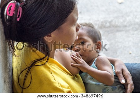 LAGUNA, PHILIPPINES - DECEMBER 4, 2015: Woman breast feeding a child seeking alms at church portal ruins.  A common scene found in many Third World Countries.