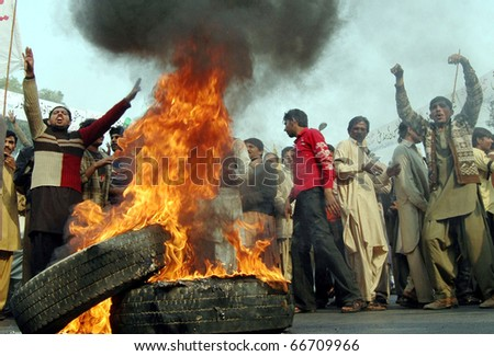 LAHORE, PAKISTAN - DEC 06: Traders stand near burning tires as they are protesting against electric load shading and in favor of their demands during a demonstration on December 06, 2010 in Lahore, Pakistan. - stock photo