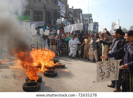 LAHORE, PAKISTAN - MAR 05: Traders of Shah Alam Market burn tyres as they are protesting against the Provincial and Federal Governments during a demonstration on March 05, 2011in Lahore.