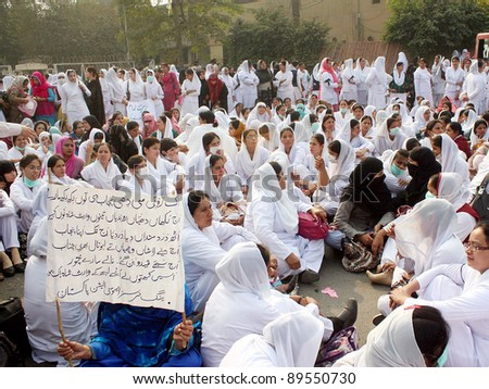 LAHORE, PAKISTAN - NOV 25: Supporters of Nurses Association Punjab are protesting in favor of their demands during demonstration at American Centre on November 25, 2011 in Lahore. - stock photo