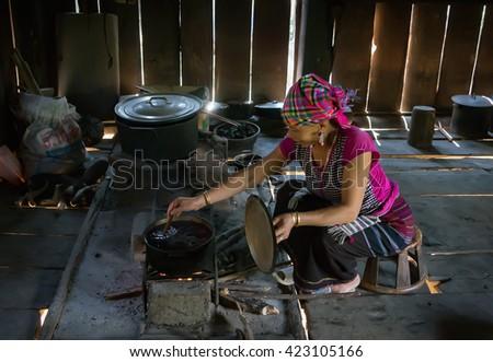 LAI CHAU, VIETNAM, May 17, 2016 LU ethnic woman, unnamed, highland Lai Chau, Vietnam, cooking, wood stove - stock photo