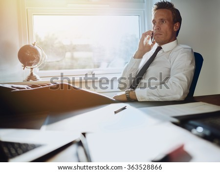 Laid back confident business man sitting at his desk with feet up talking on phone with documents on his desk - stock photo