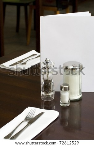 laid table of a fine dining restaurant with menu card, pepper caster and salt shaker.