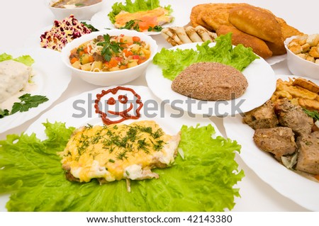 laid table with many dishes on white plates - stock photo