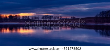 Lake after sunset landscape. Close up of opposite shore of lake with trees and sky reflected in water. Beautiful landscape. - stock photo