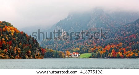Lake Alpsee on a foggy autumn day with colorful foliage on lakeside mountains and New Swanstone Castle ( Schloss Neuschwanstein ) on mountaintop in the background in Hohenschwangau, Bavaria, Germany - stock photo