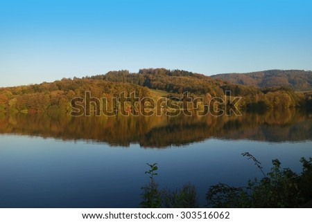 Lake and colorful wood at autumn with reflections at water