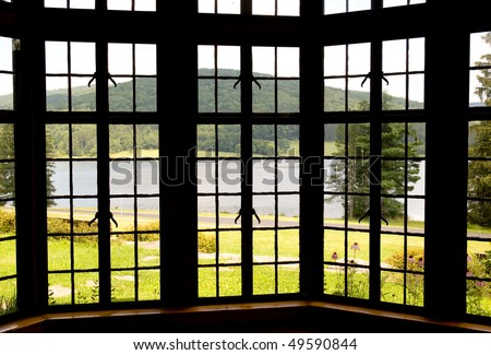 lake and forest through a bay window - stock photo