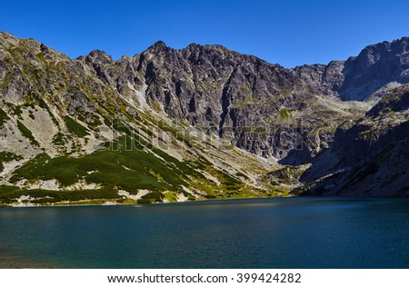Lake and rocky peaks in the High Tatras mountains in Poland - stock photo