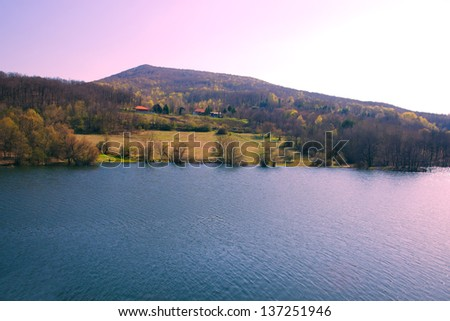 Lake and shore with forest and mountains - stock photo