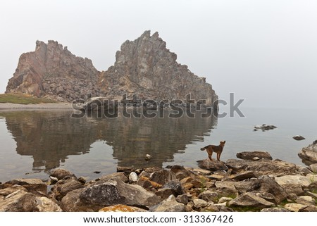 Lake Baikal. View on the natural sights of the Olkhon Island - Shamanka Rock  at overcast foggy morning - stock photo