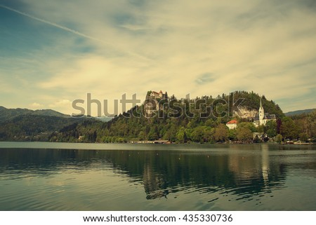Lake Bled is a glacial lake in the Julian Alps in northwestern Slovenia, where it adjoins the town of Bled and is overlooked by Bled Castle.  - stock photo