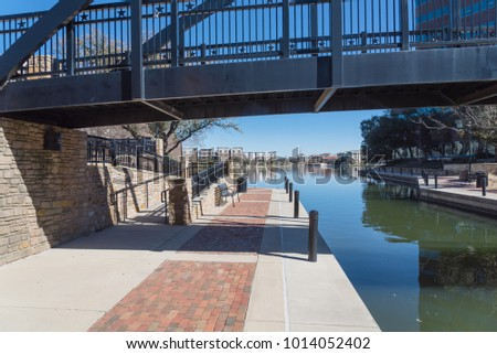 Lake Carolyn and Mandalay Canal Walk intersection in Las Colinas, Irving, Texas. Step-free access, riverside walkway, bench, bridge and lakeside apartment building complex in the distance.