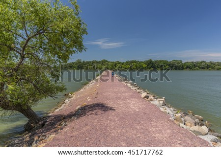 Lake Causeway To Island with a woman walking. - stock photo