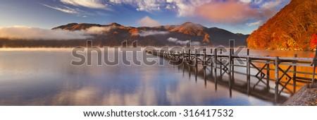 Lake Chuzenji (Chuzenjiko) near Nikko in Japan. Photographed on a beautiful still morning in autumn at sunrise. - stock photo