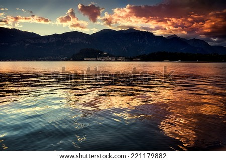 Lake Como, Italy. Panoramic view of a dramatic sunrise on the lake. Outdoors, nature, European travel and vacation concept. - stock photo