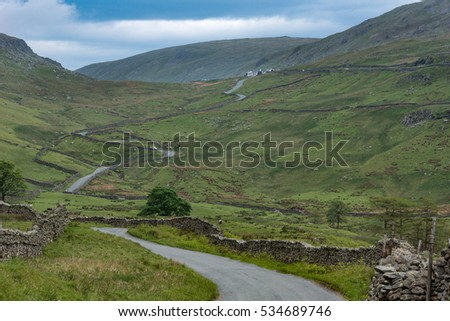Lake District, England - May 30, 2012: Long rural road with stone walls on the side meanders through the wide landscape. Shot from hill. Green meadows, lone trees, mountain slopes. Farm on horizon.