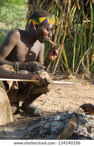 LAKE EYASI, TANZANIA - FEBRUARY 18: An unidentified man from Hadza tribe, smokes a traditional pipe, on February 18, 2013 in Tanzania. Hadzabe tribe threatened by extinction.