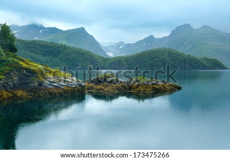 Lake (fjord) and rainy view to Svartisen Glacier (Norway)