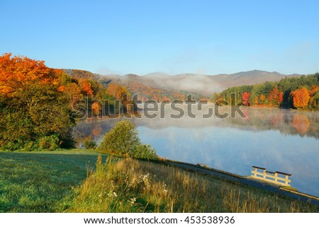 Lake fog in park with Autumn foliage and mountains with reflection in New England Stowe - stock photo