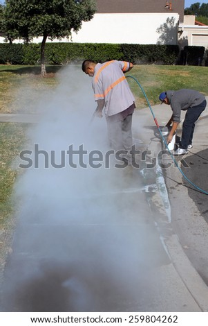 Lake Forest California - March 010,.2015 : Workers use hot water steam pressure washers and paint remover to eliminate graffiti spray painted on to a city sidewalk. - stock photo