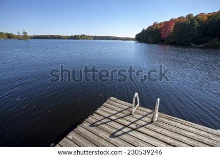 Lake in Autumn Algonquin Muskoka Ontario colors dock - stock photo